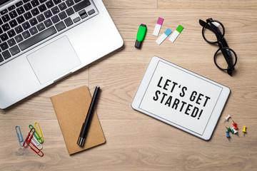 Let's get started written on tablet lying on desk as flatlay