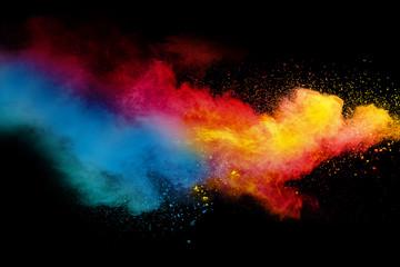 Abstract multicolored powder splatter on black background,Freeze motion of color powder splash. Color dust explosion on background.
