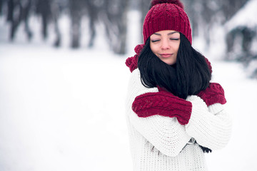 A sweet, tender and sensual young woman in a white sweater and a bright hat, scarf and mittens