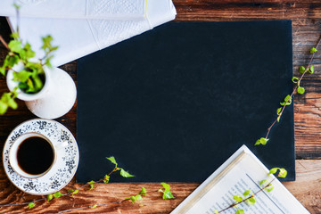 a Cup of coffee, books, a vase with green branches on a background of graphite Board, top view copyspace