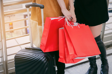 midsection two young woman holding many colorful red shopping bags and luggage walking together in modern city, winter and summer sale, promotion, mid year sale, payment and shopping online concept