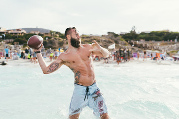 Young man bearded playing american football in the sea