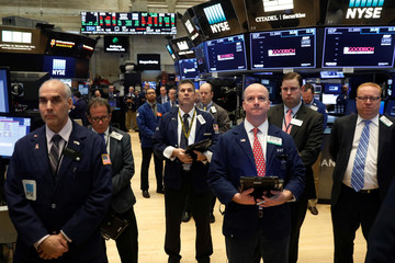 Traders pause for a moment of silence in response to a shooting at Marjory Stoneman Douglas High School in Parkland, Florida on the floor of the New York Stock Exchange shortly before the opening bell in New York