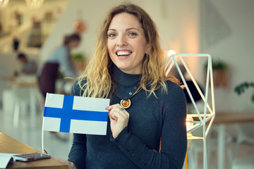 Scandinavian woman holds the flag of Finland in the background on the premises of the cafe.
