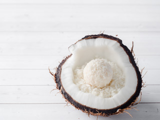 Half of the fresh organic coconut with Coconut and chocolate candy inside on wooden background