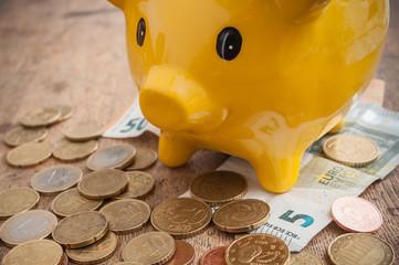 tirrelire jaune en forme de cochon et euros en billets et pièces de monnaie sur table en bois