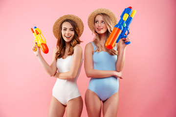 Portrait of a two cheerful girls dressed in swimsuits