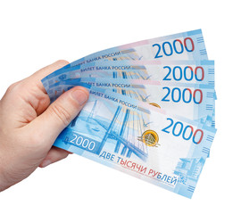 New Russian banknotes denominated in 2000 rubles in a male hand isolated on a white background