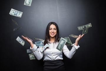 Young Business woman is standing in the rain of the dollar bills on black background