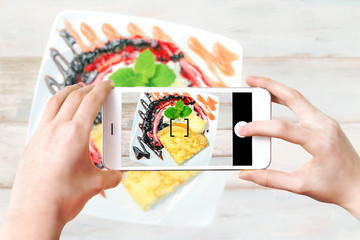 Composite image of making culinary photo on a smartphone - woman's hands holding mobile phone and touching shutter button on the screen.