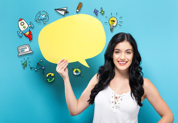 Young woman holding a yellow speech bubble