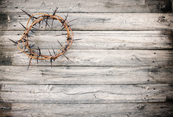 Easter Jesus crucifixion and a crown of thorns on old wood background