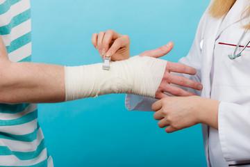 Doctor bandaging sprained wrist.