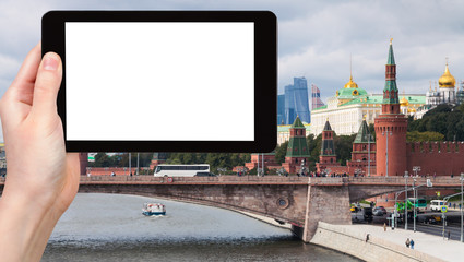 tourist photographs bridge and Kremlin in Moscow
