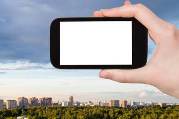 tourist photographs Moscow skyline with park