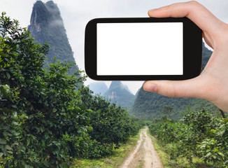 tourist photograps road to karst peaks in Yangshuo