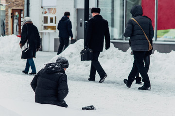 homeless man begs for alms knees in the snow