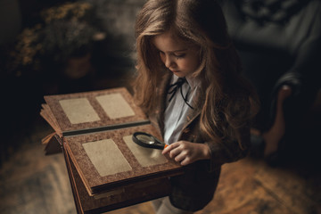 Child girl in image of Sherlock Holmes stands in room and looks photoalbum with magnifier on background of old interior. Closeup.