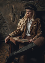 Young pensive woman in image of Sherlock Holmes sits in armchair and holds photoalbum in her hands with magnifier on background of old interior.