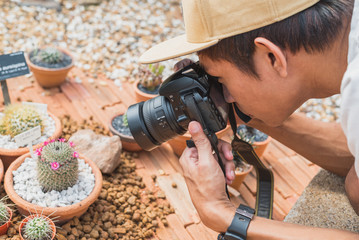 Young man takes macro photo with DSLR camera. Enthusiastic Asian photographer shoots a blooming plant (cactus) from the short distance