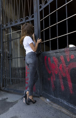 girl in jeans, high heels shoes with long hair is kept behind bars