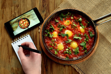 Fried eggs in tomato sauce in a cast iron pan and a smartphone next to it. Woman's hand is writing a plan in the notebook on wooden background