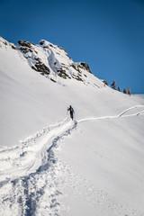 Skitour Spur im Gelände unter blauem Himmel