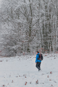 Man with a winter blue jacket having a backpack walking away from forest, on a snowy path