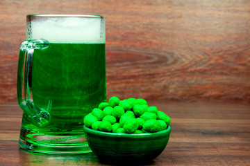 Saint Patrick's Day. Green glass pint of beer and green snacks cookies sweets on wooden background