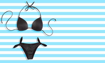 Black bikini bathing suit on the light blue stripe background. Summer fashion image.