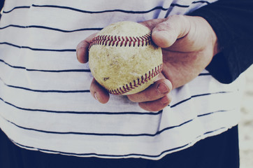 Baseball pitcher holds rough looking ball to pitch.  Sports image for american sport, background or graphic.