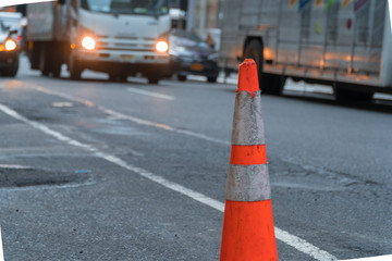 Road cone on side of busy city street to caution drivers around dangerous conditions