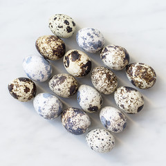 Quail eggs are laid out in the form of a rectangle diagonally on the marble surface