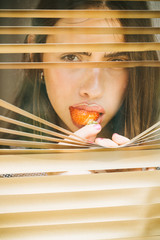 Girl eat red strawberry and look in window