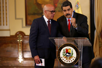 Venezuela's President Nicolas Maduro listens to Venezuela's Communications and Information Minister Jorge Rodriguez during a news conference in Caracas