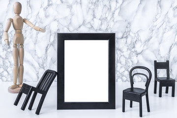 White desk, marble gray wall, black vertical empty frame, small chairs and wooden doll