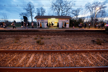 Commuters walk near rail tracks at the French state-owned railway company SNCF station of Castelnau d'Estretefonds