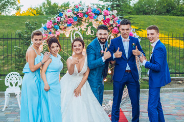 elegant stylish happy guests and bride and groom having funny photos on the background of arch, photo booth. Wedding moments with bridesmaids and groomsmen.