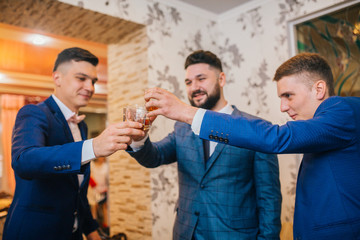 Groom and groomsmen look funny standing in the hotel room and drinking whiskey. Best friends on wedding day.