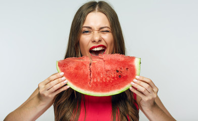 Fun portrait of young woman with big piece of watermelon