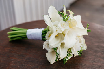 A wedding bouquet of white flowers lies on a round table