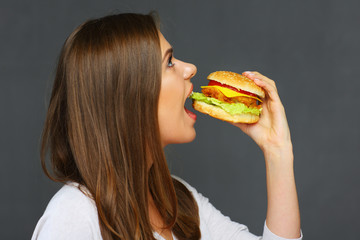Young woman eating burger fast food. Isolated portrait against gray wall.