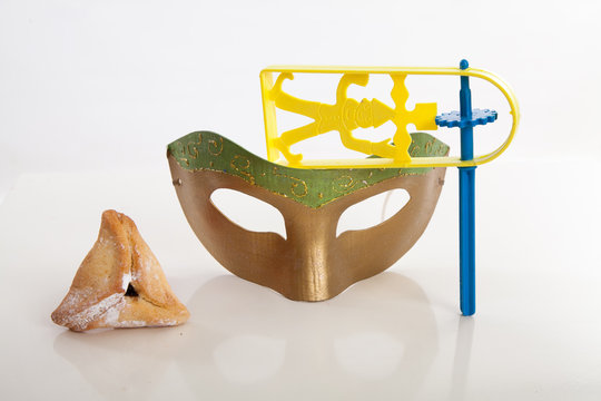 handmade green gold mask with hamantaschen Purim cookie and noisemaker on white studio background