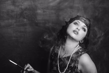 brunette girl in black dress in the style of decadence holds the mouthpiece and blows smoke