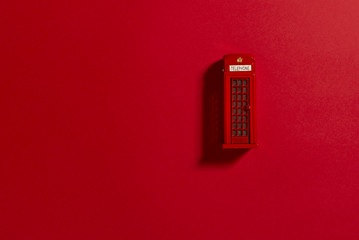 Red phone box on a red background.