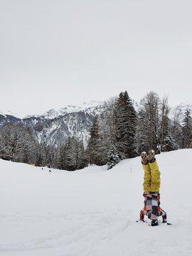Boy doing a handstand in the snow, Braunwald, Glarus, Switzerland
