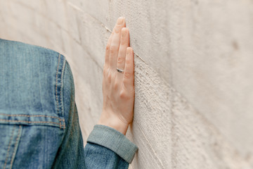 White woman hand touches the wall. Closeup of religion fingers on the stone ancient street wall.