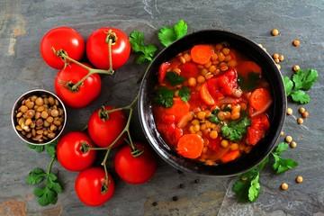 Homemade tomato, lentil soup, overhead scene, flat lay on a dark slate background