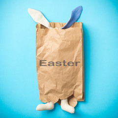 Easter bunny in a paper bag. Blue background. Easter eggs. Space for text. Black lettering easter. Easter 2018.