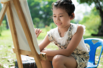 Asian children cute or kid girl painting water color on  paper and nature meadow at garden or public park for fun and preschool education on holiday relax